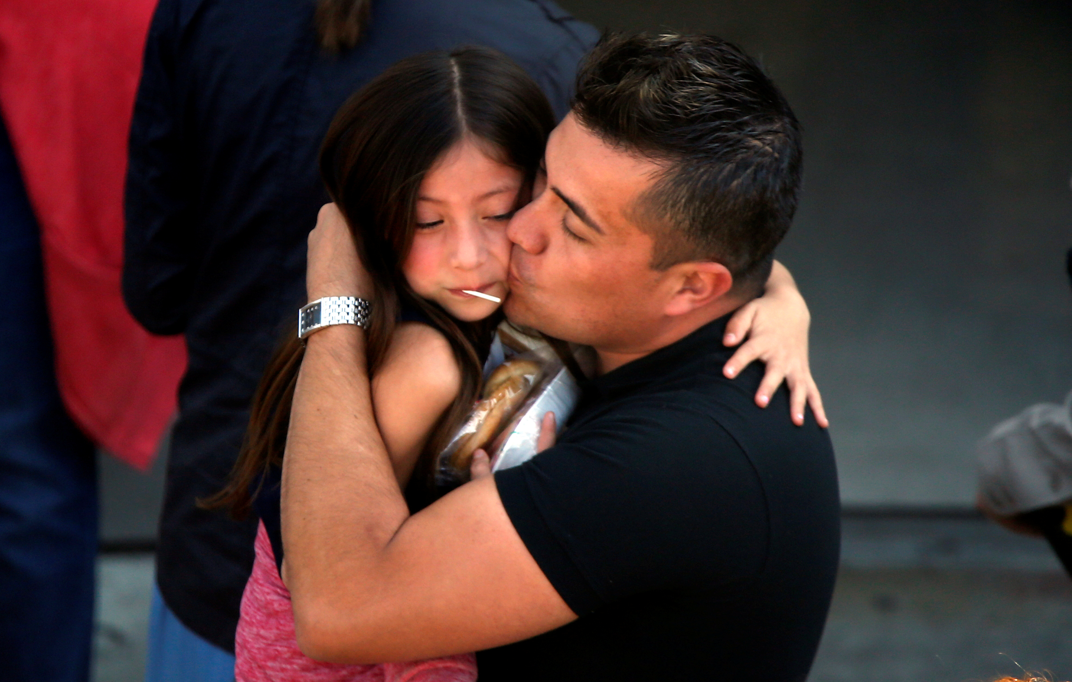 A student who was evacuated after a shooting at North Park Elementary School is embraced after groups of them were reunited with parents waiting at a high school in San Bernardino, Calif. (REUTERS/Mario Anzuoni)