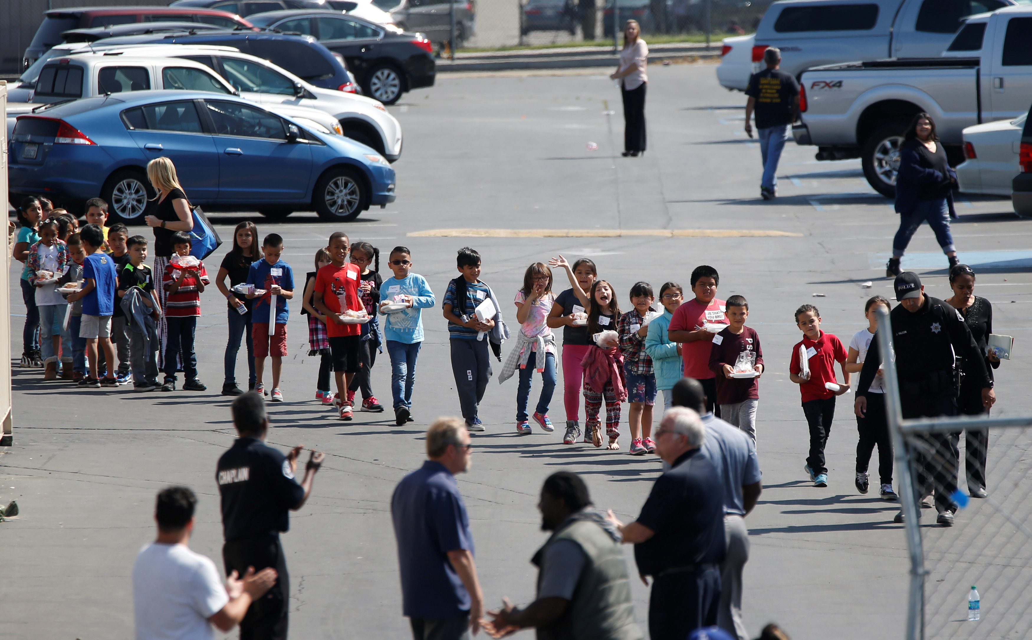 Students who were evacuated after a shooting at North Park Elementary School walk past well-wishers to be reunited with their waiting parents at a high school in San Bernardino, Calif., on April 10, 2017. (REUTERS/Mario Anzuoni)