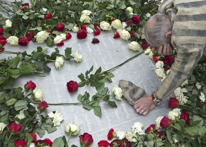 Nazi concentration camp survivor Alexander Bytschok of Kiev, Ukraine, mourns on a metal plaque during ceremonies commemorating the 72nd anniversary of the liberation of the former Nazi concentration camp Buchenwald near Weimar, Germany, on April 11, 2017. (AP Photo/Jens Meyer)