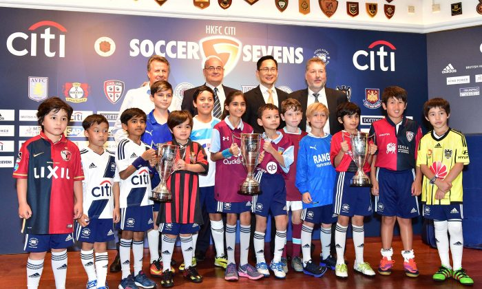 (Back Row L-R) Tony Bratsanos (Organiser), Mark Sutcliffe (HKFA), Wayne Fong (Citi), Chis Plowman (Tournamanent Director), together wth children representing overseas clubs, at the 2017 HKFC Citi Soccer Sevens draw on Tuesday April 11. The competition will take place at HKFC from May 26 to 28. (Bill Cox/Epoch Times)