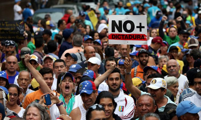 "Demonstrators rally against Venezuela's President Nicolas Maduro carrying a sign that reads ""No more dictatorship"" in Caracas, Venezuela on April 13, 2017. (REUTERS/Carlos Garcia Rawlins)"