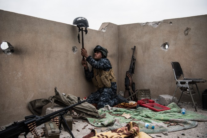 An Iraqi federal policeman uses a helmet on a stick to try and draw fire from an ISIS sniper in an attempt to make him reveal his position during the battle to recapture west Mosul in Iraq on April 13. (Carl Court/Getty Images)