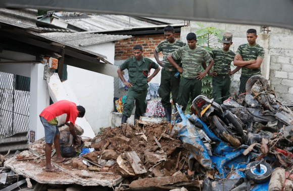 A man opens a bag next to military officers during a rescue mission after a garbage dump collapsed and buried dozens of houses in Colombo, Sri Lanka April 15, 2017. (REUTERS/Dinuka Liyanawatte)