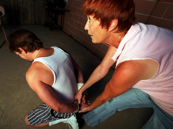 Retired bounty hunter Dottie Thorson handcuffs a fugitive at a friend's home in Reseda, Calif. on July 27, 2000. (Photo by Dan Callister/Online USA)