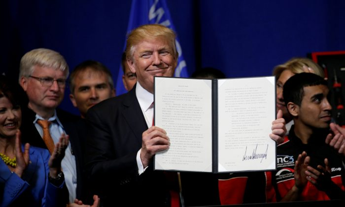 President Donald Trump smiles after signing an executive order directing federal agencies to recommend changes to a temporary visa program used to bring foreign workers to the United States to fill high-skilled jobs during a visit to the world headquarters of Snap-On Inc, a tool manufacturer in Kenosha, Wisconsin on April 18, 2017.  (REUTERS/Kevin Lamarque)