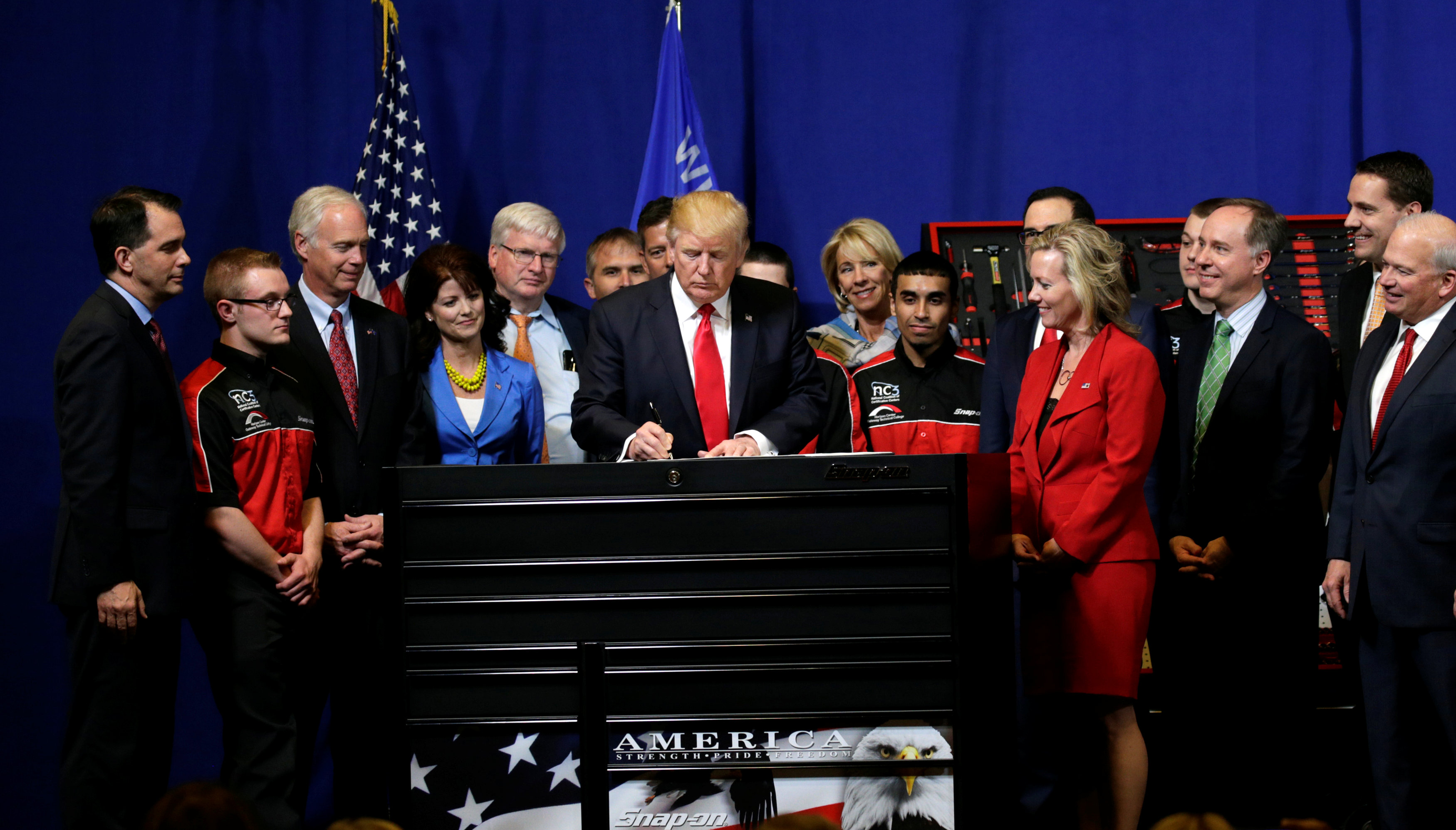 President Donald Trump signs an executive order directing federal agencies to recommend changes to a temporary visa program used to bring foreign workers to the United States to fill high-skilled jobs during a visit to the world headquarters of Snap-On Inc, a tool manufacturer in Kenosha, Wis., on April 18, 2017.  (REUTERS/Kevin Lamarque)