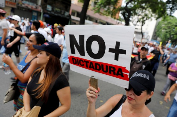 """Demonstrators rally during the so-called """"mother of all marches"""" with a sign that reads """"No more dictatorship"""" against Venezuela's President Nicolas Maduro in Caracas, Venezuela April 19, 2017. (REUTERS/Carlos Garcia Rawlins)"""