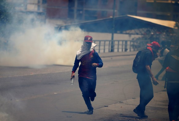 """Demonstrators clash with riot police during the so-called """"mother of all marches"""" against Venezuela's President Nicolas Maduro in Caracas, Venezuela April 19, 2017. (REUTERS/Carlos Garcia Rawlins)"""