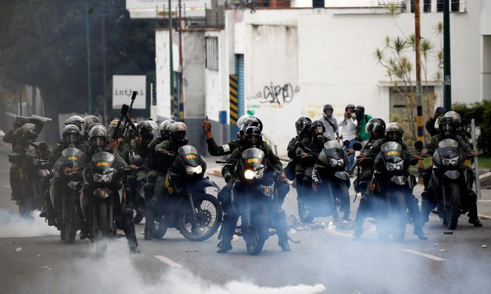 """Riot police take position while clashing with demonstrators during the so-called """"mother of all marches"""" against Venezuela's President Nicolas Maduro in Caracas, Venezuela on April 19, 2017. (REUTERS/Carlos Garcia Rawlins)"""