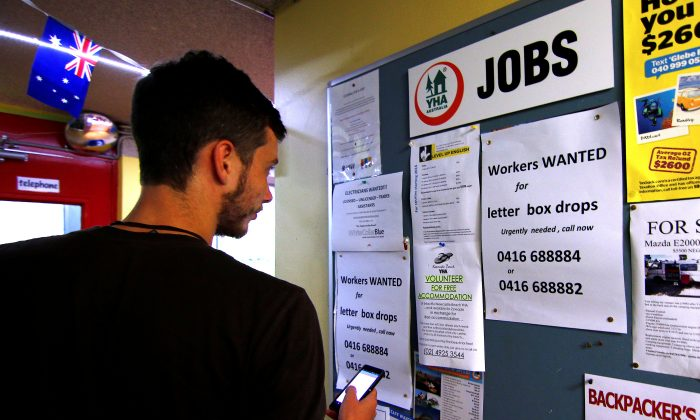 A man uses his phone to record a job add posted on a notice board at a backpacker hostel in Sydney, Australia on May 9, 2016. (REUTERS/Steven Saphore)