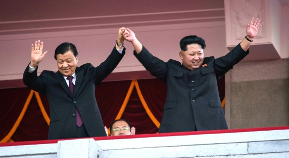 North Korea's leader Kim Jong-Un (R) and Chinese Politburo standing committee member Liu Yunshan (L) wave from a balcony towards participants of a mass military parade at Kim Il-Sung square in Pyongyang on October 10, 2015. North Korea was marking the 70th anniversary of its ruling Workers' Party. (ED JONES/AFP/Getty Images)