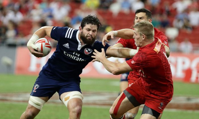 Danny Barrett of USA fends off a challenge from John Moonlight of Canada during the Cup Final 2017 Singapore Sevens match between USA and Canada at National Stadium on April 16, 2017 in Singapore. (Suhaimi Abdullah/Getty Images)
