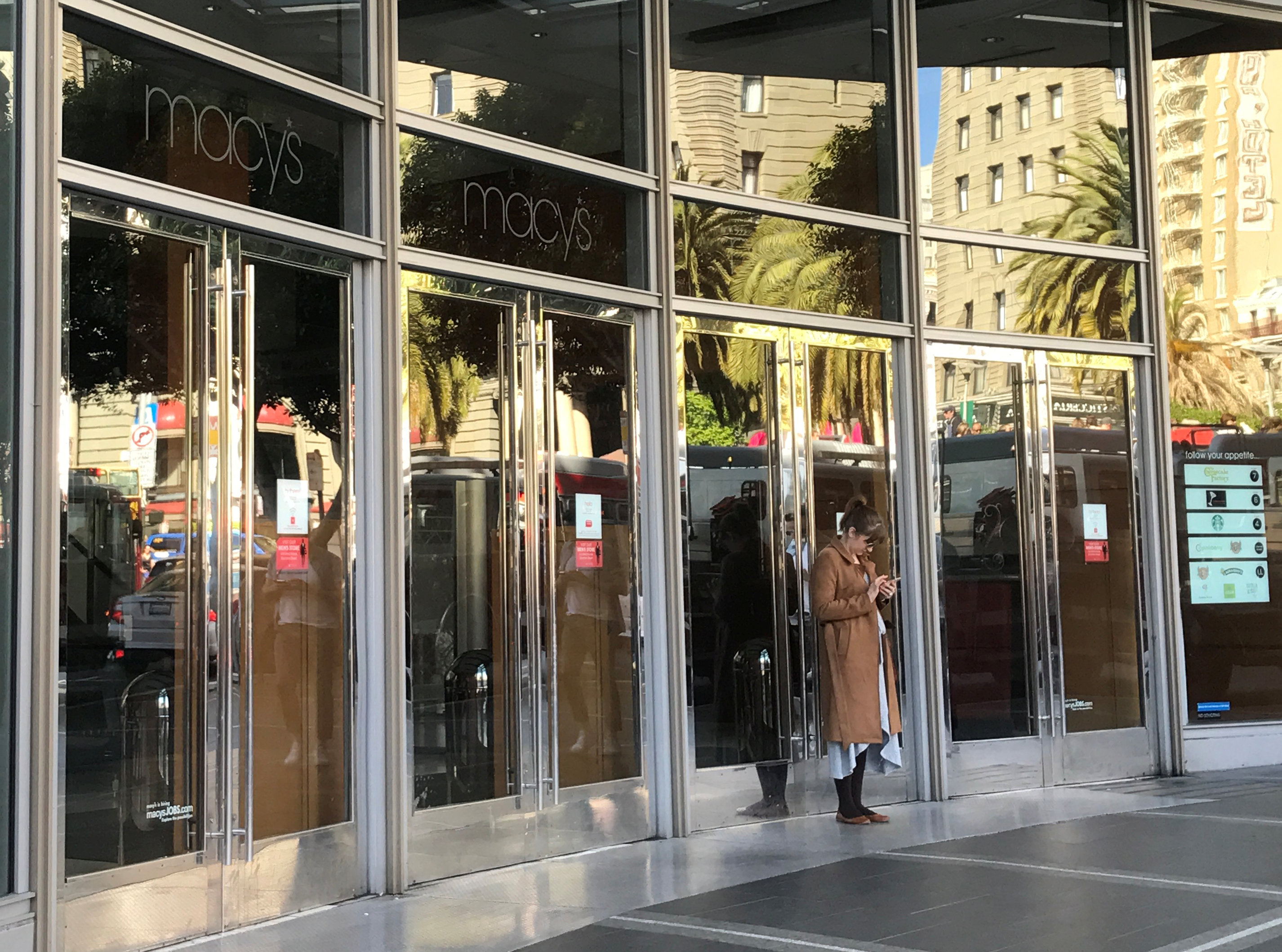 An employee stands outside the closed doors of Macy's department store, during a power cut in San Francisco, Calif., April 21, 2017.  (REUTERS/Alexandria Sage)
