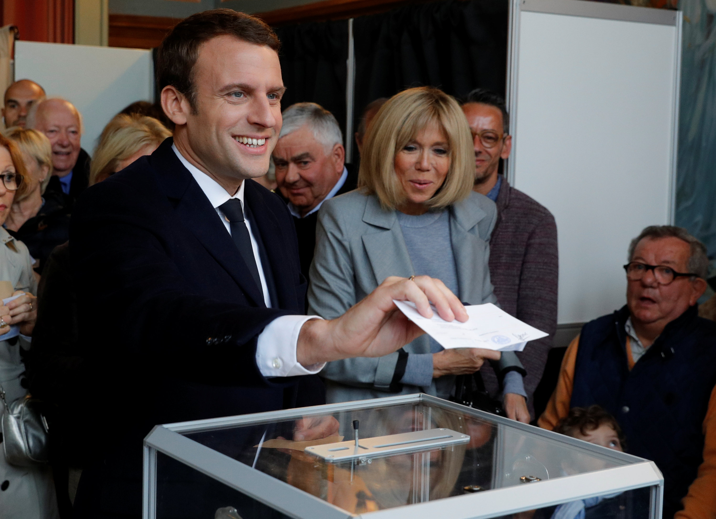 Emmanuel Macron (L), head of the political movement En Marche !, or Onwards !, and candidate for the 2017 French presidential election, casts his ballot in the first round of 2017 French presidential election at a polling station in Le Touquet, northern France on April 23, 2017. (REUTERS/Philippe Wojazer)
