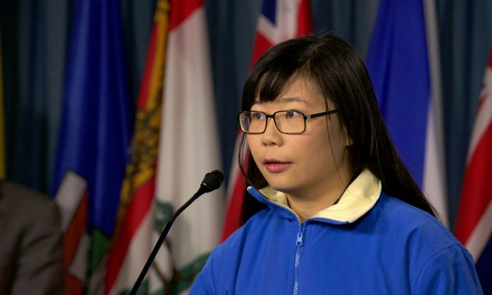 Hope Chen speaks to reporters on Parliament Hill on Dec. 9, 2015. The 22-year-old has been trying to draw attention to the plight of her father who was imprisoned in China for suing former Chinese leader Jiang Zemin. Chen was threatened by a Chinese agent for discussing his detention in the media. (Matthew Little/Epoch Times)