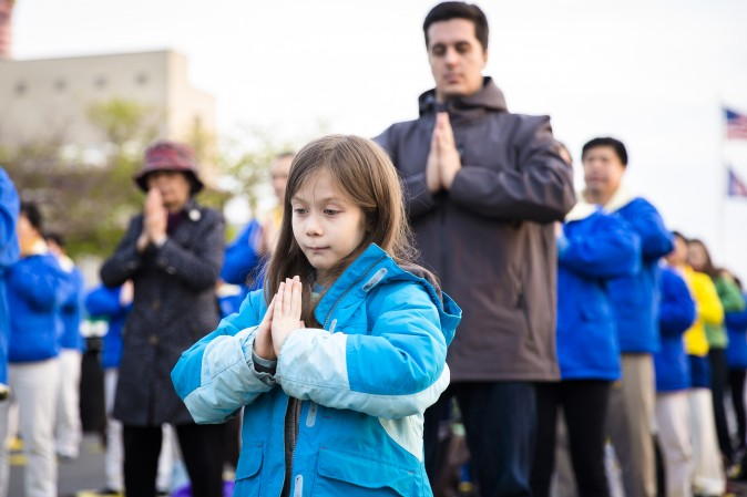A young Falun Gong practitioner attends a candlelight vigil near the Chinese Consulate in New York on April 23, 2017. (Samira Bouaou/The Epoch Times)