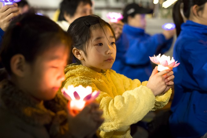 Young Falun Gong practitioner attend a candlelight vigil near the Chinese Consulate in New York on April 23, 2017. (Samira Bouaou/The Epoch Times)