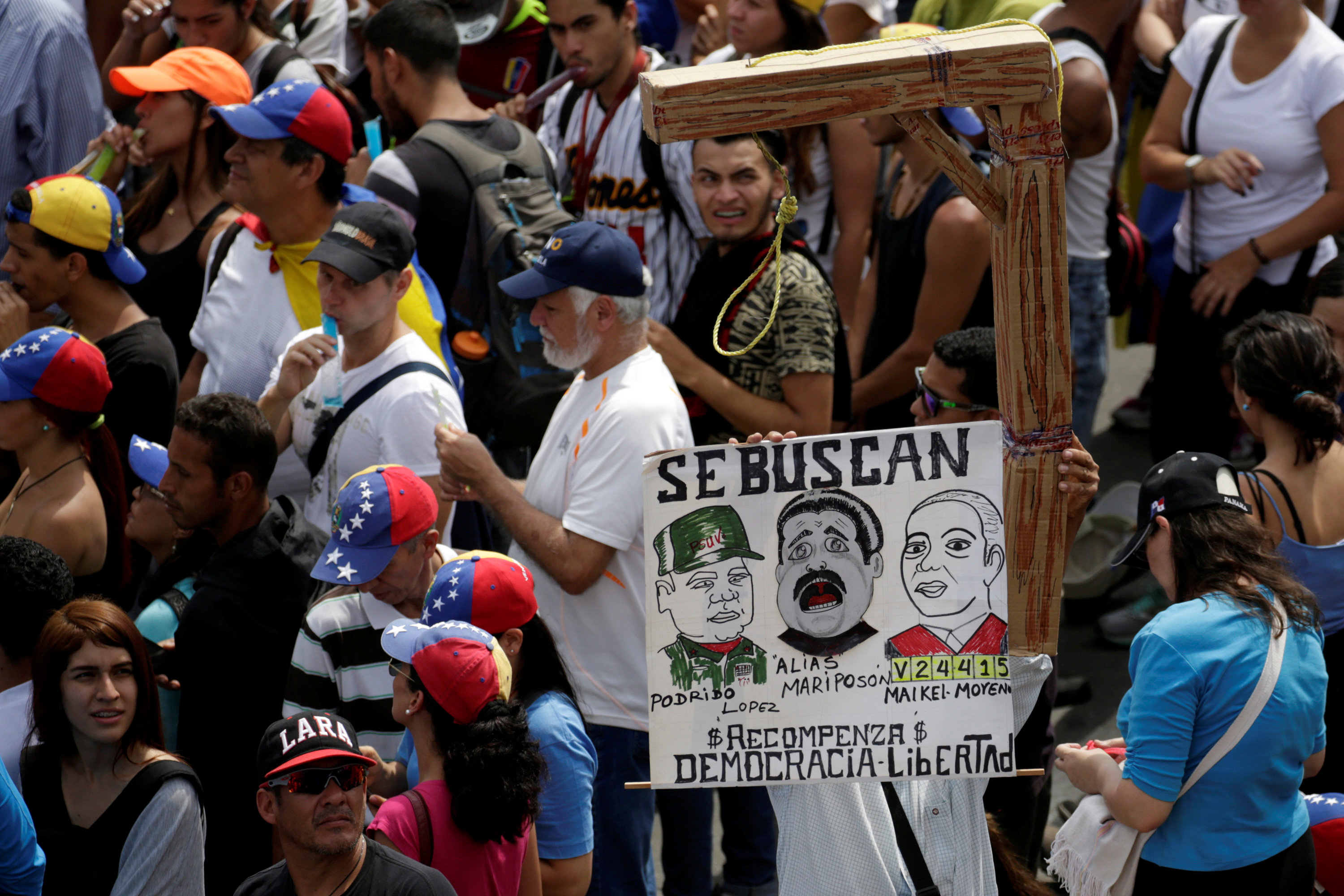 "Protesters carry a placard depicting (L-R) Venezuela's Defense Minister Vladimir Padrino Lopez, Nicolas Maduro and Venezuela's Supreme Court President Maikel Moreno that reads ""Wanted"" during a rally in Caracas, Venezuela on April 24, 2017. (REUTERS/Marco Bello)"