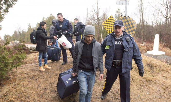 Asylum seekers claiming to be from Yemen are arrested by RCMP officers after crossing the border from New York into Hemmingford, Quebec, on March 8, 2017. (The Canadian Press/Ryan Remiorz)