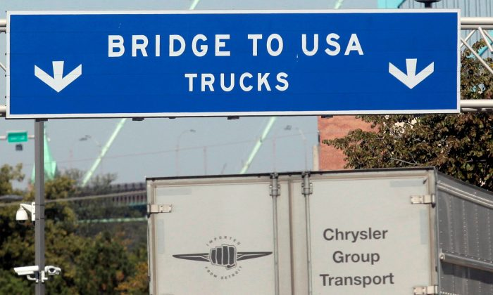 A commercial automotive supplier truck passes under a sign leading to the Ambassador bridge crossing over to Detroit, Michigan from Windsor, Ontario September 28, 2013. (REUTERS/Rebecca Cook)