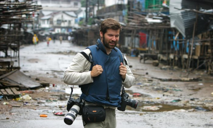 Getty Images photographer Chris Hondros walks through the streets on Aug. 3, 2003, in Monrovia, Liberia. Hondros, who was on assignment in Misrata, Libya, was killed on April 20, 2011 by a rocket-propelled grenade (RPG). (Nic Bothma/EPA via Getty Images)