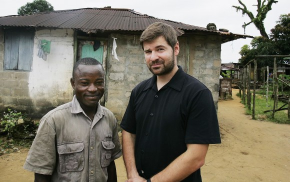 """MONROVIA, LIBERIA - OCTOBER 05:  Joseph Duo (L), 28, a former Liberian government soldier, poses with photographer Chris Hondros at his home October 5, 2005 in Monrovia, Liberia.  A picture of Duo jumping into the air in exultation during a battle with rebel forces in 2003 was distributed around the world, making him a symbol of the intractable difficulties of Liberia's long civil war. Duo, now de-commissioned by the United Nations and unemployed, lives in a squalid neighborhood on the outskirts of Monrovia with a wife and three children, but his fame lives on. He's well known among Monrovians and is often stopped by people who recognize him from the photo. He is unapologetic about his military career, which began at the start of the Liberian civil war in 1990, when he was 14. """"You have to adapt yourself to the system, and that's the system I found myself in,"""" he says, """"I fought in the interest of the people."""" (Photo by Getty Images)"""