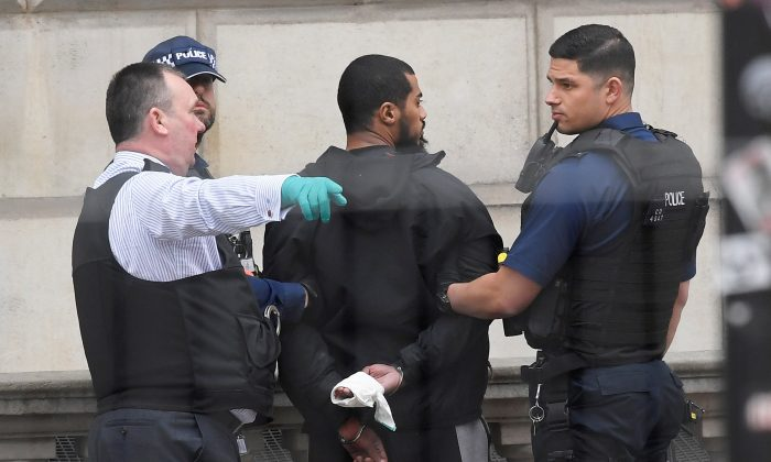 A man is held by police in Westminster after an arrest was made on Whitehall in central London, Britain on April 27, 2017. (REUTERS/Toby Melville)