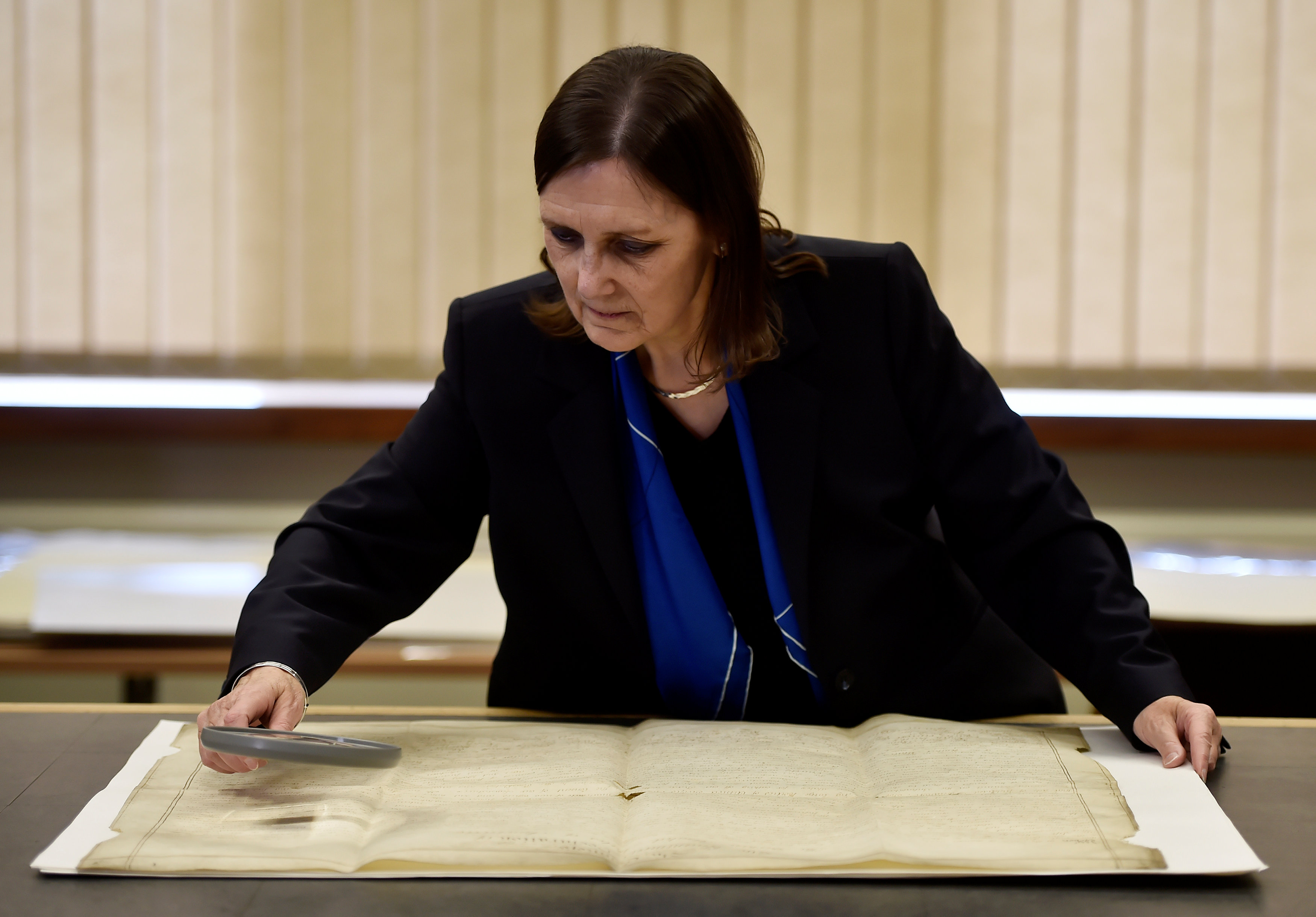 West Sussex County Archivist, Wendy Walker looks at a rare handwritten copy of the U.S. Declaration of Independence at the West Sussex Record Office in Chichester in south England, Britain on April 27, 2017. (REUTERS/Hannah McKay)
