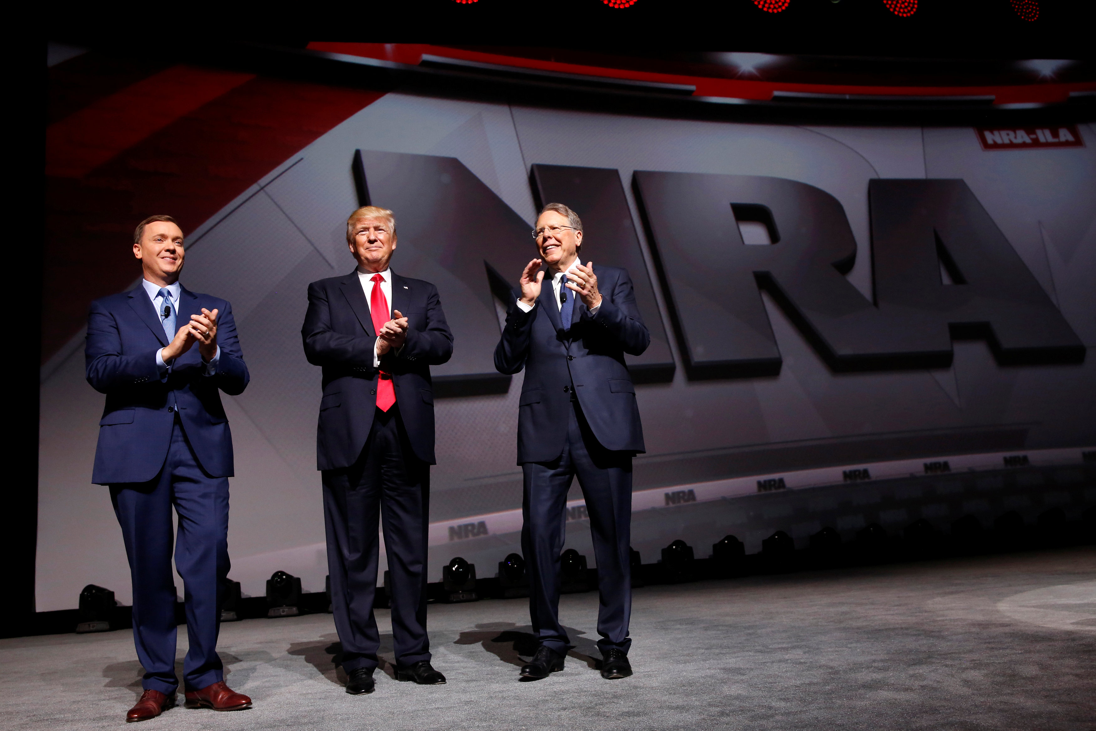 NRA Executive Director Chris Cox (L) and Executive Vice President and CEO Wayne LaPierre (R) welcome President Donald Trump (C) onstage to deliver remarks at the National Rifle Association (NRA) Leadership Forum at the Georgia World Congress Center in Atlanta, Ga., on April 28, 2017. (REUTERS/Jonathan Ernst)