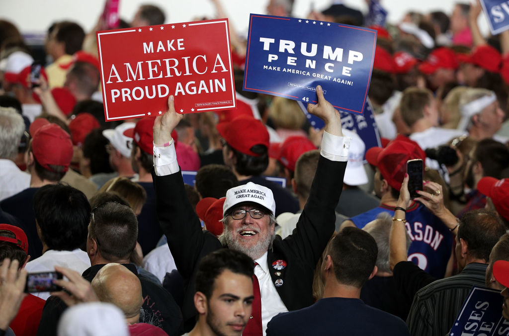 "A supporter holds up signs during a ""Make America Great Again Rally"" at the Pennsylvania Farm Show Complex & Expo Center in Harrisburg, Pa., on April 29, 2017. (Alex Wong/Getty Images)"