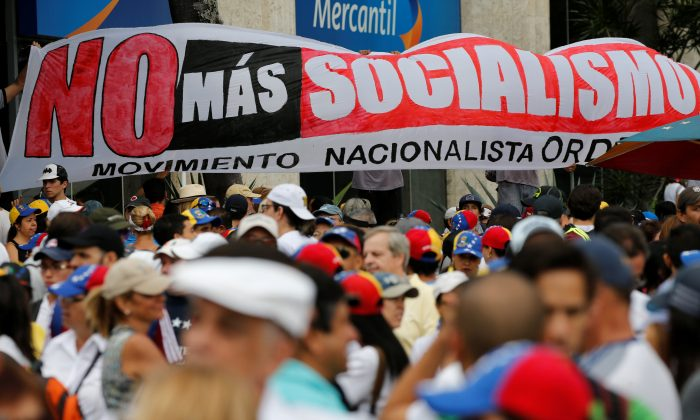 Demonstrators hold a placard reads: 'No more Socialism' while rallying against Venezuela's socialist leader Nicolas Maduro in Caracas, Venezuela on May 1, 2017. (REUTERS/Carlos Garcia Rawlins)