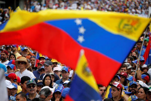 Demonstrators hold Venezuelan flags