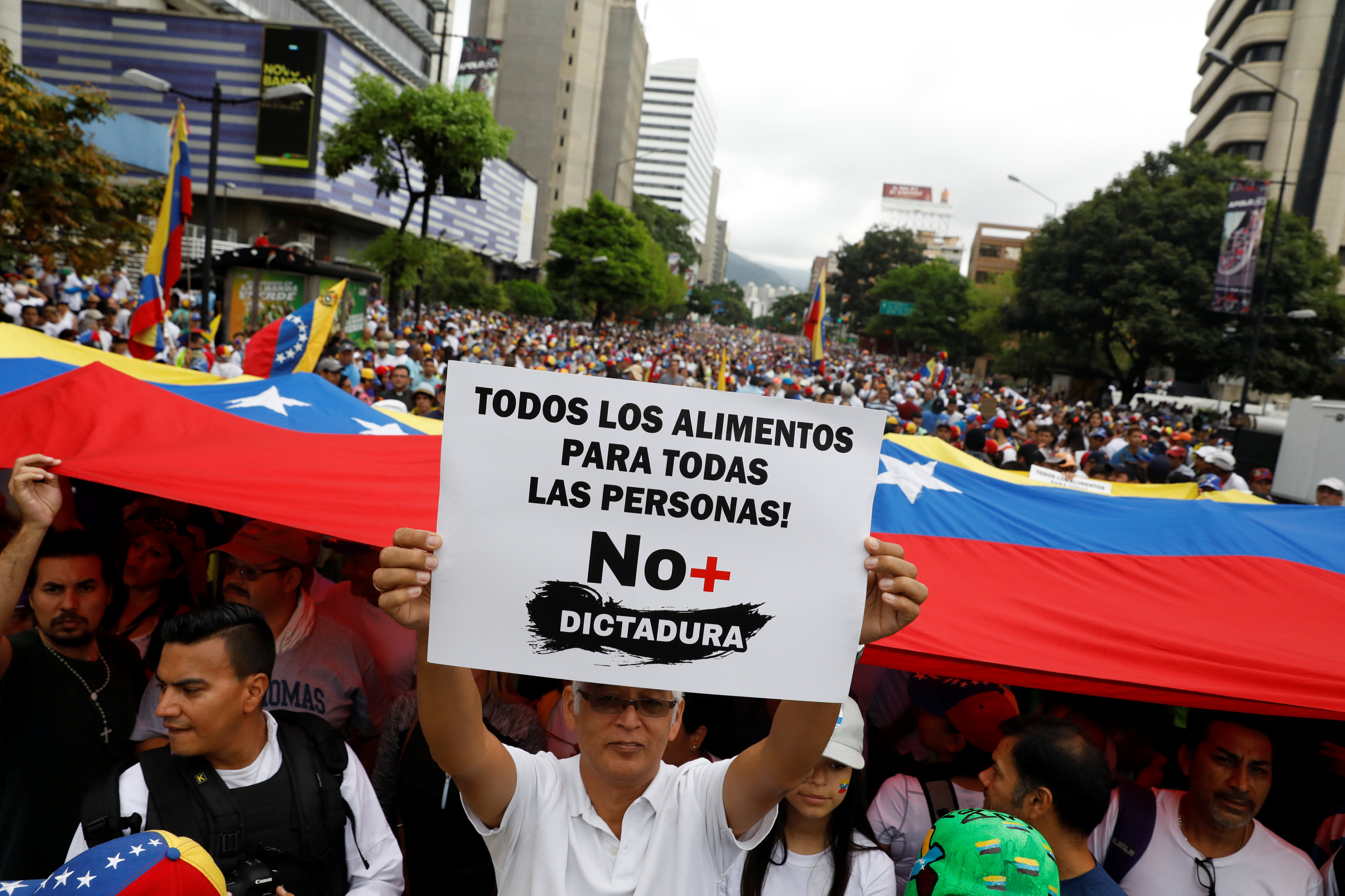 Demonstrators hold Venezuelan flags and a sign reads: ' All the food for all the people! No more dictatorship ' while rallying against Venezuela's President Nicolas Maduro in Caracas, Venezuela on May 1, 2017. (REUTERS/Carlos Garcia Rawlins)