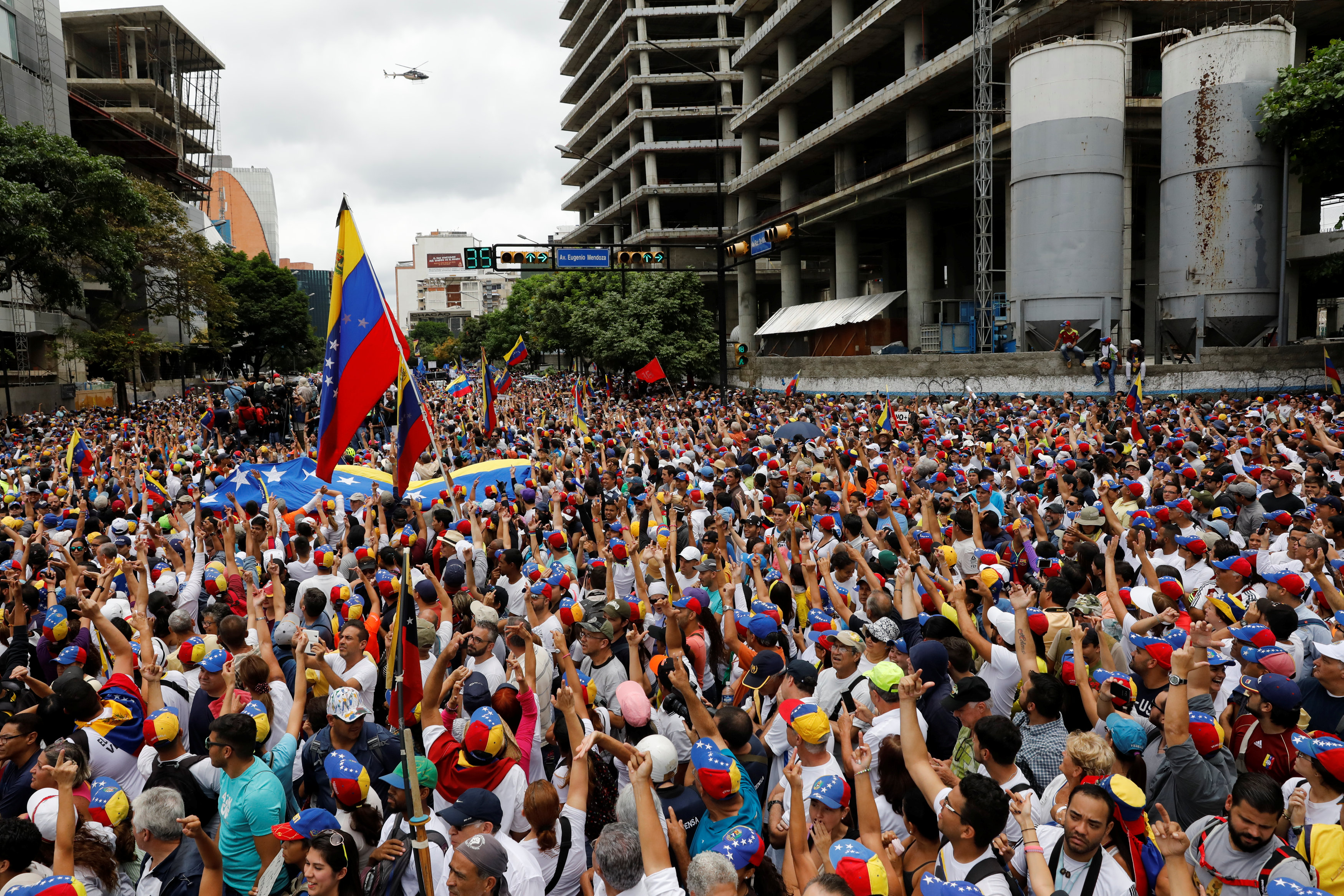 Demonstrators wave as the helicopter passes while rallying against Venezuela's President Nicolas Maduro in Caracas, Venezuela on May 1, 2017. (REUTERS/Carlos Garcia Rawlins)