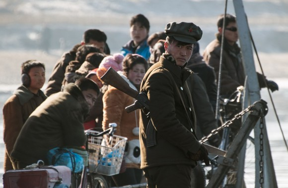 A North Korean soldier stands guard on a boat with locals on the Yalu River near the town of Sinuiju across from the Chinese border town of Dandong on Feb. 9, 2016. (JOHANNES EISELE/AFP/Getty Images)