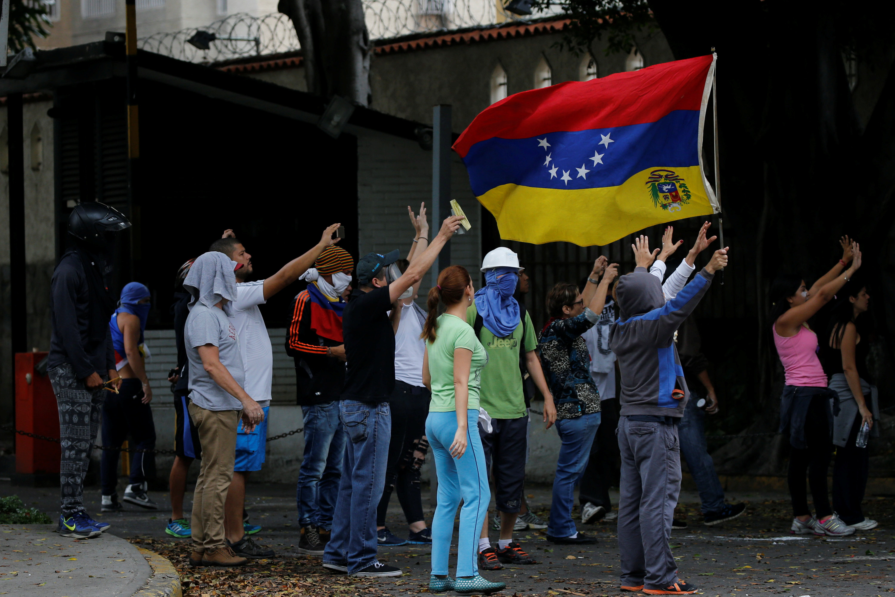 Opposition supporters wave a Venezuelan national flag as they clash with Venezuelan National guards during a protest against Venezuela's President Nicolas Maduro's government in Caracas, Venezuela on May 2, 2017. (REUTERS/Carlos Garcia Rawlins)