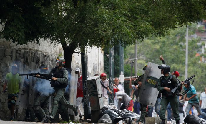 Venezuelan National guards fire tear gas toward opposition supporters during a protest against Venezuela's President Nicolas Maduro's government in Caracas, Venezuela May 2, 2017. (REUTERS/Carlos Garcia Rawlins)