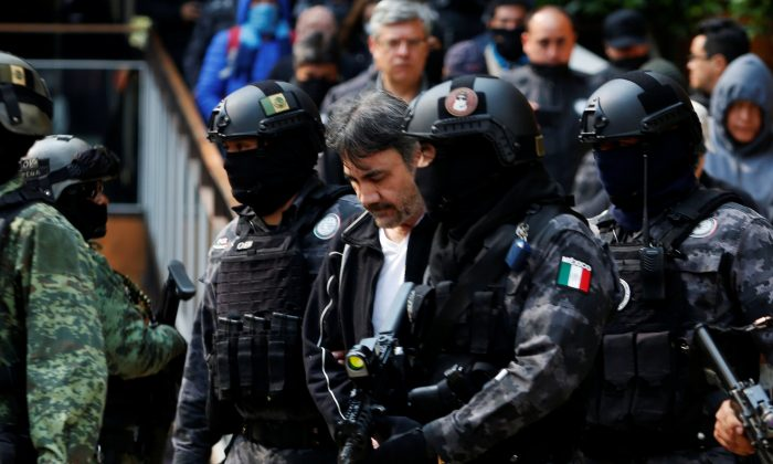 "Accused drug kingpin Damaso Lopez (C), nicknamed ""The Graduate"", is escorted by police officers in Mexico City, Mexico on May 2, 2017. (REUTERS/Carlos Jasso)"
