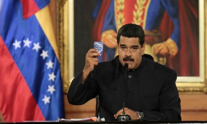Venezuela's socialist leader Nicolas Maduro holds a copy of the Venezuelan constitution as he speaks during a ceremony at Miraflores Palace in Caracas, Venezuela on May 1, 2017. (Miraflores Palace/Handout via REUTERS)