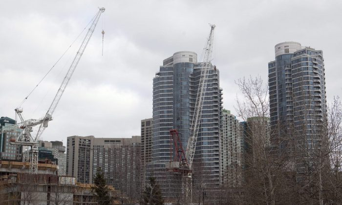 Construction cranes stand in front of condominiums in downtown Toronto, Feb. 4, 2012. A growing contingent of Canadian families are opting for the compact condo lifestyle as space runs out in Canada's biggest cities and housing prices remain out of reach for many. (The Canadian Press/Pawel Dwulit)