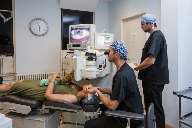 Dr. Steven Stetson holds the Femtosecond laser and demonstrates how a patient would be positioned during the KAMRA inlay procedure in his office at Diamond Vision in New York on Aug. 26, 2016. (Samira Bouaou/Epoch Times)