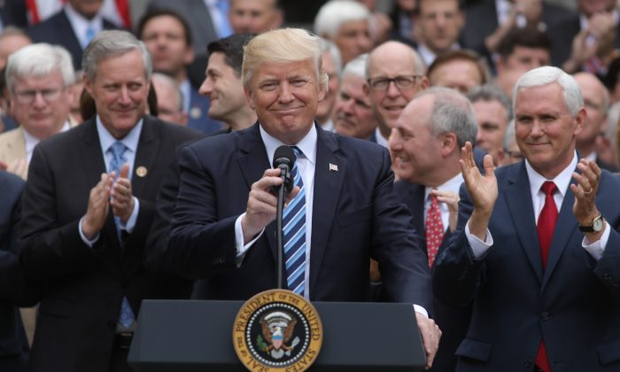 President Donald Trump (C) gathers with Vice President Mike Pence (R) and Congressional Republicans in the Rose Garden of the White House after the House of Representatives approved the American Healthcare Act, to repeal major parts of Obamacare and replace it with the Republican healthcare plan, in Washington on May 4, 2017. (REUTERS/Carlos Barria)