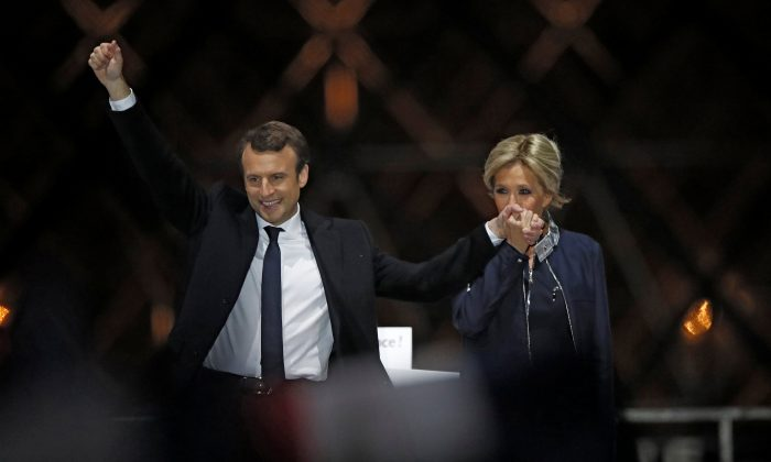 French President elect Emmanuel Macron and his wife Brigitte Trogneux on the stage at his victory rally near the Louvre in Paris, France on May 7, 2017. (REUTERS/Christian Hartmann)