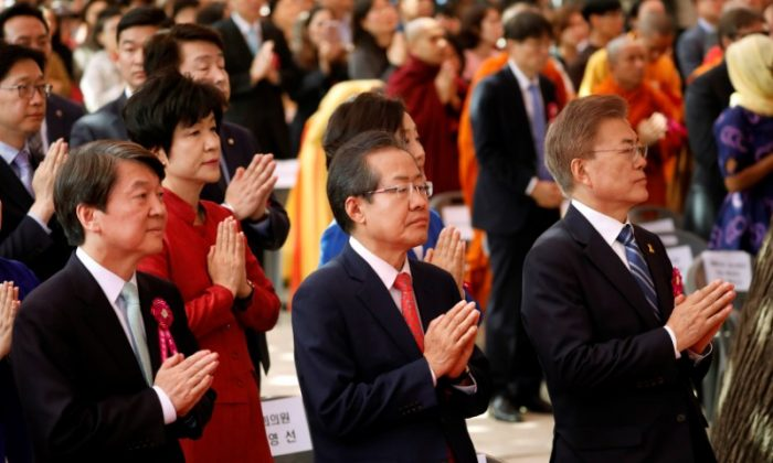 Ahn Cheol-soo, presidential candidate of the People's Party, Hong Joon-pyo, presidential candidate of the Liberty Korea Party, and Moon Jae-in, presidential candidate of the Democratic Party of Korea, during a ceremony celebrating the birthday of Buddha at Jogye temple in Seoul, South Korea on May 3, 2017. (REUTERS/Kim Hong-Ji)