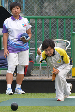 Eva Hui (delivering) from Shatin Sports Association on her way to winning the semi-final of the National Fours against the Island Lawn Bowls Club skipped by Vivian Wong.  They will face Indian Recreation Club in the Finals Day on July 9. (Stephanie Worth)