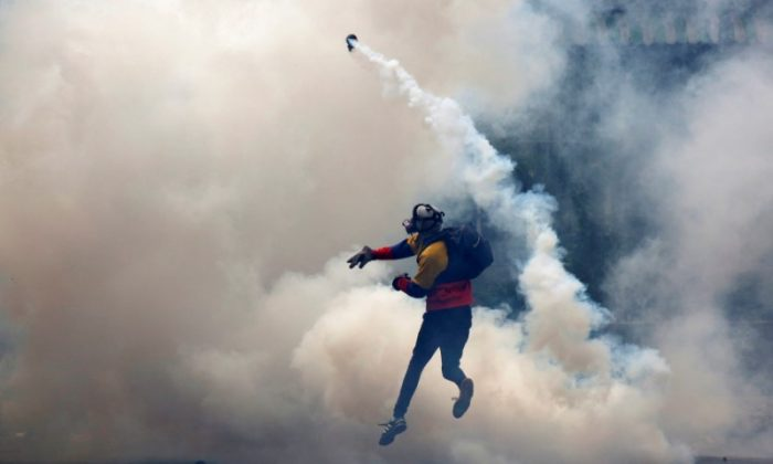 An opposition supporter clashes with riot police during a rally against President Nicolas Maduro in Caracas, Venezuela on May 8, 2017. (REUTERS/Carlos Garcia Rawlins)