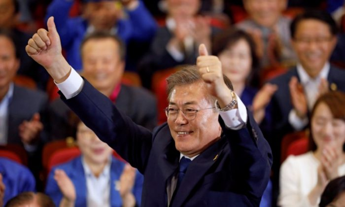 Moon Jae-in, the presidential candidate of the Democratic Party of Korea, poses for photographs as he watches a television report on an exit poll of the presidential election in Seoul, South Korea on May 9, 2017. (REUTERS/Kim Hong-Ji)