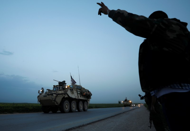 A Kurdish fighter from the People's Protection Units (YPG) gestures at a convoy of U.S military vehicles driving in the town of Darbasiya next to the Turkish border, Syria on April 28, 2017. (REUTERS/Rodi Said)