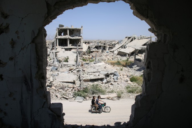 Syrians ride a motorbike past destroyed buildings in a rebel-held area of the southern city of Daraa on May 9, 2017. (MOHAMAD ABAZEED/AFP/Getty Images)