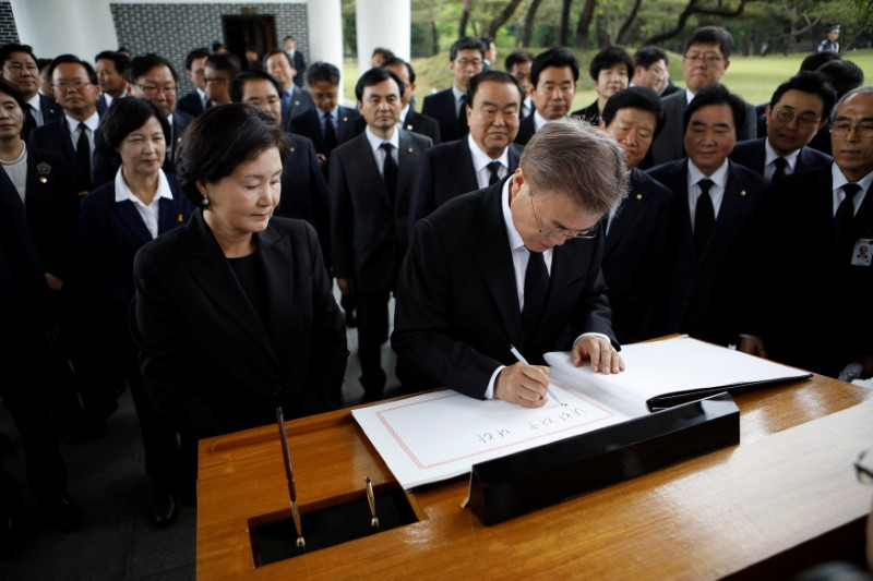 South Korea's President Moon Jae-in writes in a visitor's book at the National Cemetery in Seoul, South Korea on May 10, 2017. (REUTERS/Kim Hong-Ji)